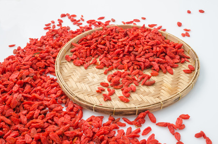 penetrate: Dried goji berries prepare for women who want to penetrate the fat and eyesight on basket and white background.