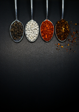 peppery: Spicy seasoning. Thai spices on spoon. Pepper and caryenne pepper. Stock Photo