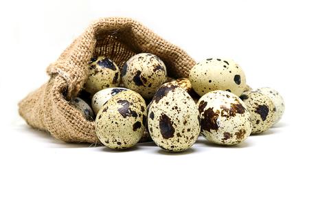 흰색 배경에 삼 베 자루에 메 추 라 기 계란입니다. 메추라기 알에는 높은 수준의 비타민 A와 B2가 있습니다.