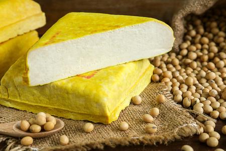 黄色の豆腐と大豆、木製の皿の上のベジタリアン料理。大豆から作られた豆腐は自然にグルテン フリー、低カロリーです。 写真素材