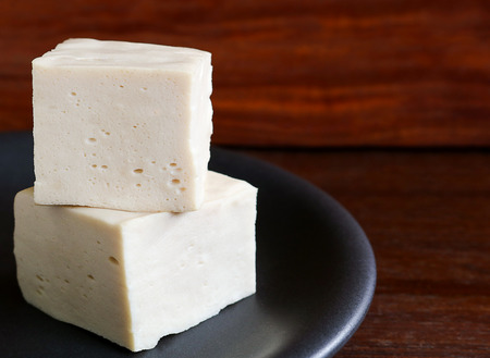 soy tofu or bean curd, vegetarian food on wooden background. tofu made from soybean is naturally gluten-free and low calorie