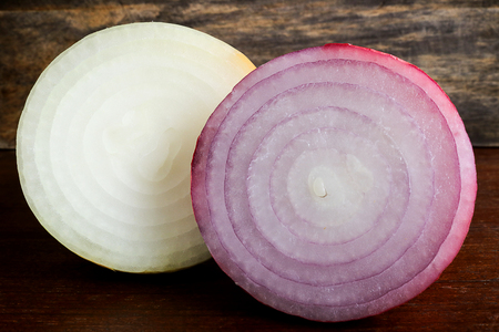 fresh red onion on wooden background. Onions are a nutrient-dense food and a lot of health benefits, High fiber, Vitamin C, strong antioxidant and prevention colorectal cancers