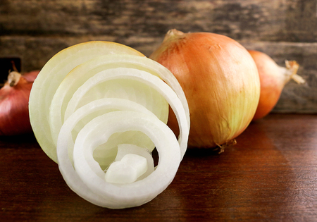 fresh onion and onion rings on wooden background. Onions are a nutrient-dense food and a lot of health benefits, High fiber, Vitamin C, strong antioxidant and prevention colorectal cancers Stock Photo