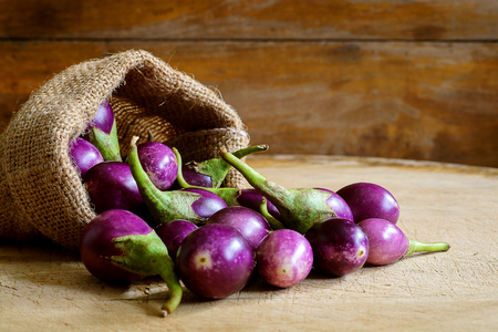 Fresh mini purple eggplant in hemp sack on wooden background. Eggplant has benefits to help build strong bones, prevent osteoporosis and cancer, help lose weight and manage diabetes.