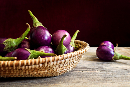 Fresh mini purple eggplant in basket on wooden background. Eggplant has benefits to help build strong bones, prevent osteoporosis and cancer, help lose weight and manage diabetes.