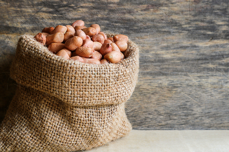 Peanuts in hemp sack on wooden background. Peanuts are rich in energy and anti-ageing. Nuts can prevent coronary artery disease, Cancer, Diabetes, Gallstones and improves memory.
