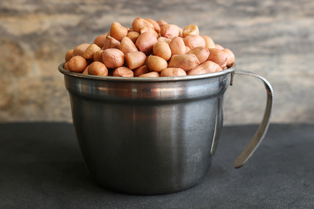 Peanuts in stainless cup on wooden background. Peanuts are rich in energy and anti-ageing. Nuts can prevent coronary artery disease, Cancer, Diabetes, Gallstones and improves memory. Stock Photo