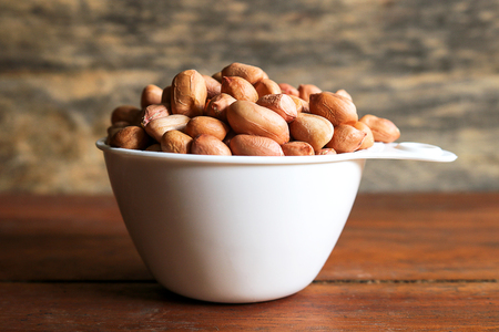 Peanuts in white measuring cup on wooden background. Peanuts are rich in energy and anti-ageing. Nuts can prevent coronary artery disease, Cancer, Diabetes, Gallstones and improves memory.