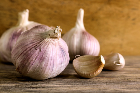 asian flavors: Garlic clove and garlic bulb on wooden background. Garlic has benefit to prevent heart disease, Cancer, Reduce blood pressure, Protect skin and help to lose weight.
