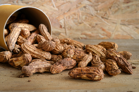 Raw peanuts in paper cans on wooden background. Peanuts are rich in energy and anti-ageing. Nuts can prevent coronary artery disease, Cancer, Diabetes, Gallstones and improves memory. Stock Photo