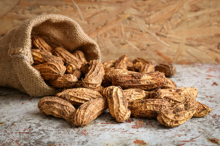 gallstones: Raw peanut in hemp sack on wooden background. Peanuts are rich in energy and anti-ageing. Nuts can prevent coronary artery disease, Cancer, Diabetes, Gallstones and improves memory.