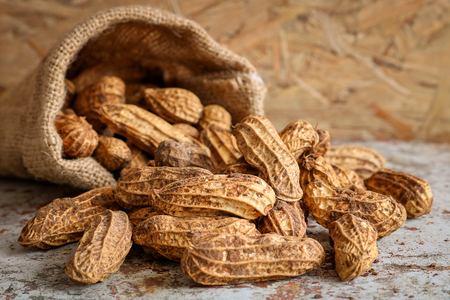 Raw peanut in hemp sack on wooden background. Peanuts are rich in energy and anti-ageing. Nuts can prevent coronary artery disease, Cancer, Diabetes, Gallstones and improves memory.