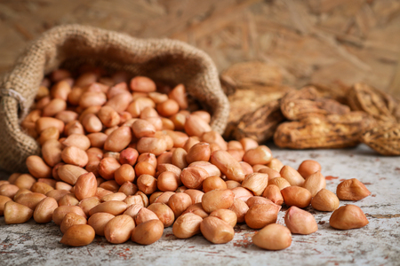 Erdnüsse im Hanfsack auf Holzuntergrund. Erdnüsse sind reich an Energie und Anti-Aging. Nüsse können koronare Herzkrankheit, Krebs, Diabetes, Gallensteine ??zu verhindern und verbessert das Gedächtnis. Standard-Bild - 85424954
