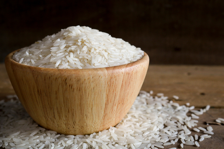 glycemic: Jasmine rice in wooden bowl on rustic wood background. Jasmine rice, also known as Thai fragrant rice or Khoa Hom Mali. Jasmine rice is delicious, nutty taste and characteristic flowery aroma. Jasmine rice contains some protein and very little fat.