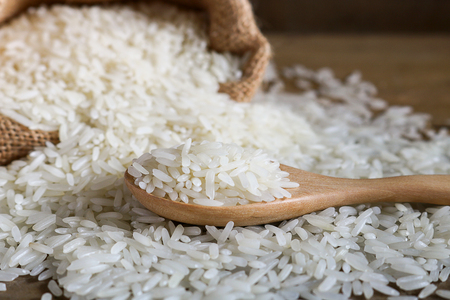 glycemic: Jasmine rice in wooden spoon on rustic wood background. Jasmine rice, also known as Thai fragrant rice or Khoa Hom Mali. Jasmine rice is delicious, nutty taste and characteristic flowery aroma. Jasmine rice contains some protein and very little fat. Stock Photo