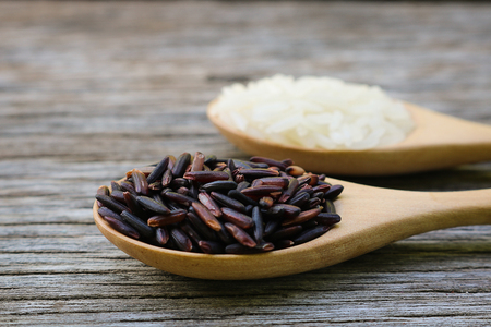 Riceberry in wooden spoon on rustic wood background. Jasmine rice and Riceberry rice its variety rice that originates from Thailand. Jasmine rice and Riceberry have delicious, nutty taste and characteristic flowery aroma and rich in many antioxidant and many health benefits Stock Photo