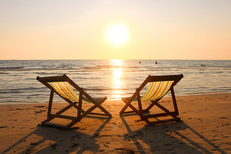 Beach chairs on the tropical beach and sea at summer sunset time. Empty beach loungers on summer holiday in tropical paradise island. Standard-Bild