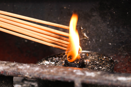 Light the incense sticks by the fire of lanterns. Buddhist is burning incense in Chinese temple.