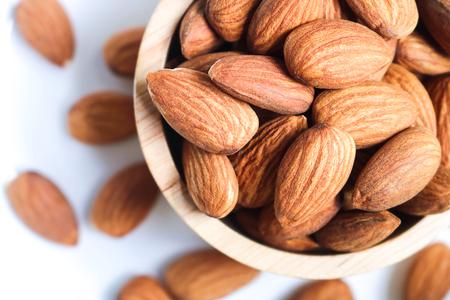 Nueces de almendra en un tazón de madera sobre fondo blanco. Las almendras son las nueces más saludables y uno de los mejores alimentos para el cerebro. Foto de archivo
