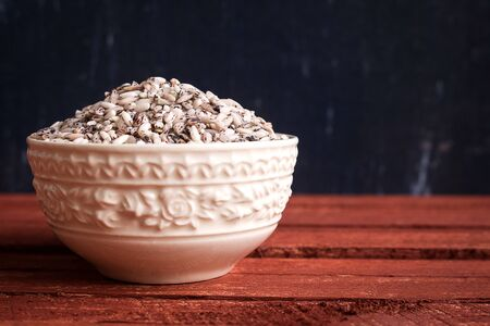 Raw organic sticky rice in white ceramic bowl. Purple rice contains more antioxidant compounds than white rice and they help protect the body's cells from harmful free radicals.