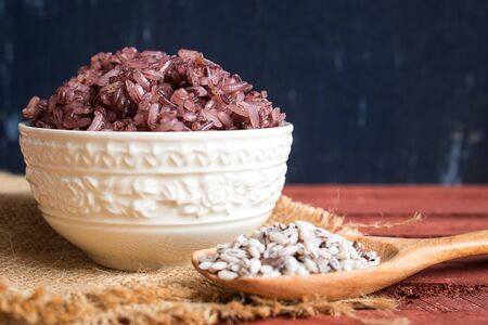 Organic sticky rice in ceramic bowl on rustic wood. Purple rice contains more antioxidant compounds than white rice and they help protect the body's cells from harmful free radicals. Stockfoto