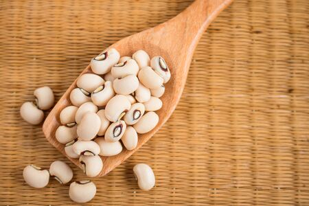 Black-eyed beans in wooden spoon on a reed mat. Black-eyed peas have health benefits, Good for help weight loss and relieving constipation.