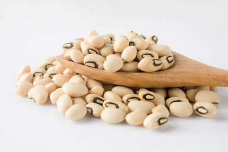 Black-eyed beans, also known as cowpeas in a wooden spoon on white background. Black-eyed peas are incredibly nutrient-dense, packing plenty of fiber and protein, good for help weight loss and relieving constipation.