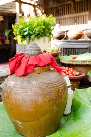 Local liquor in earthenware jar on banana leaf photo