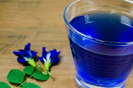 Asian pigeonwings and blue juice isolated on wood background photo