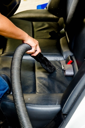 hand vacuum cleaning dirt on a car carpet in car-wash shop