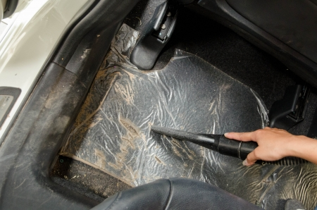 hand vacuum cleaning dirt on a carpet in car photo