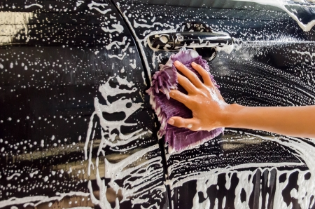 A Hand washing a car with a microfiber cloth photo