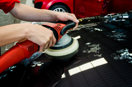 Hands with daul action polisher. polishing on car surface. hand and foam pad in blur motion from vibration  of polisher machine Stok Fotoğraf