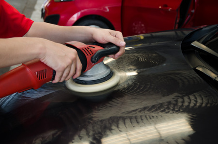polisher: Hands with daul action polisher. polishing on car surface. hand and foam pad in blur motion from vibration  of polisher machine Stock Photo