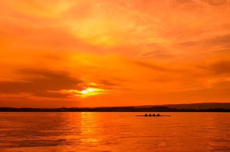 Ruderer in einem Ruderboot Silhouette auf Sonnenuntergang Hintergrund in See