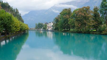 interlaken: Landscape of Interlaken village with water reflection on Aare River, Switzerland.