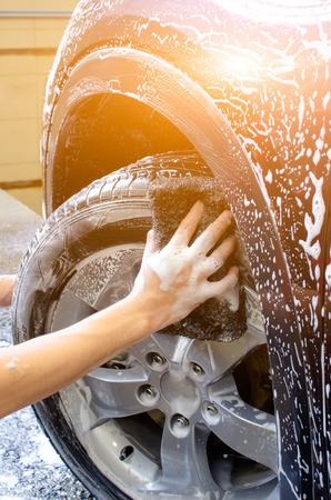 Mano de neumáticos de lavado de coches con la esponja negro Foto de archivo - 60772278