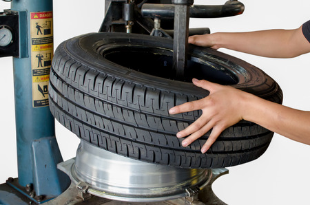 pneumatic tyres: Mechanic changing a car tire on white background Stock Photo