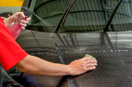 Hand polishing by clay bar and clay lubricant for remove dirt on car surface in car-wash shop