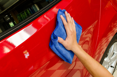 microfiber: Hand wipe red car surface with blue microfiber cloth
