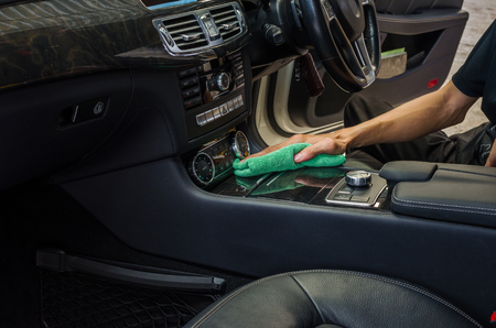 Hand with green microfiber cloth cleaning interior car. Stock Photo