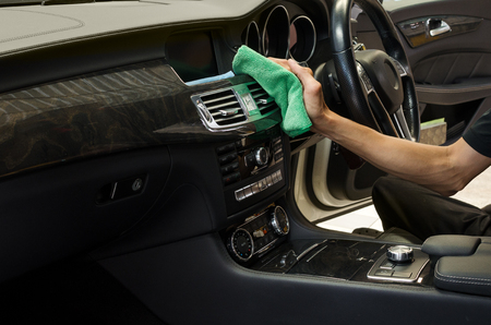 Hand with green microfiber cloth cleaning interior car. Standard-Bild