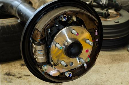 Car mechanic changing Car axle in professional car repair service.