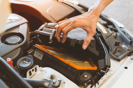 auto repair: Hand Opening Car Air Filter In Car Service Shop. Stock Photo