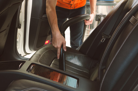 rag wheel: Cleaning of interior of the car with vacuum cleaner, Car cleaning Stock Photo