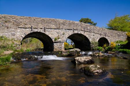 The Ancient Stone Bridge Over Dart River At Postbridge within Dartmoor National Park, Devon, England