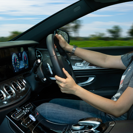 Women Drive Car with Hands On Steering Wheel. On Country Road View. Stock Photo