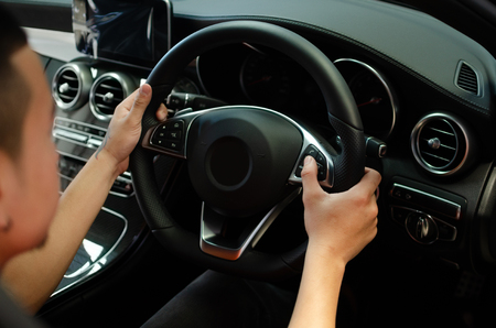 hand push Cruise control buttons on luxury car steering Stock Photo