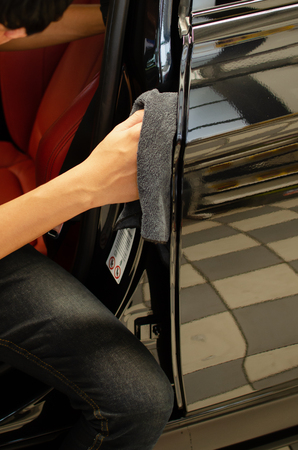 Hand with microfiber cloth cleaning door car, Fucus  On Hand Stock Photo