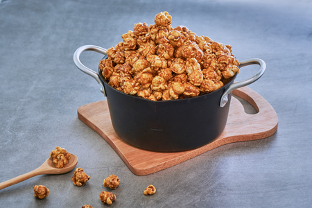 Sweet Caramel Flavoured Popcorn In Blow On Cement Table Stock Photo
